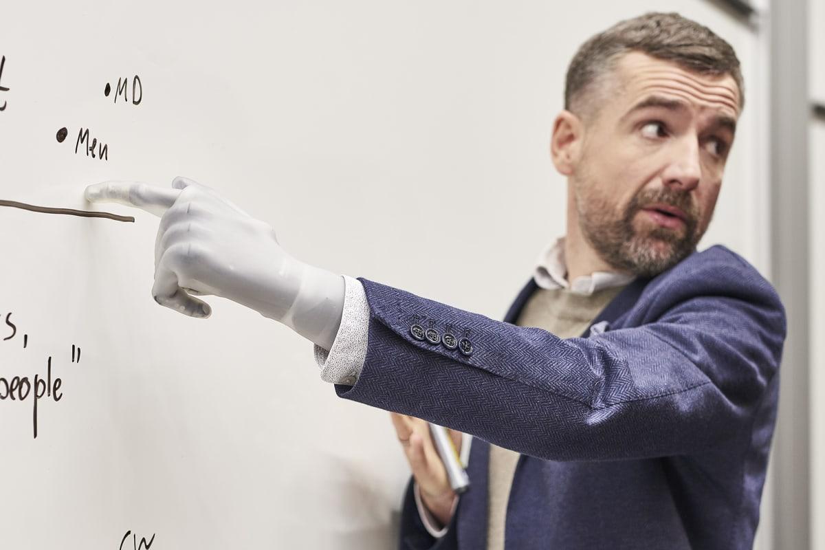 Bertolt als Professor in der Uni zeigt mit seiner Handprothese i-Limb Quantum auf ein Whiteboard