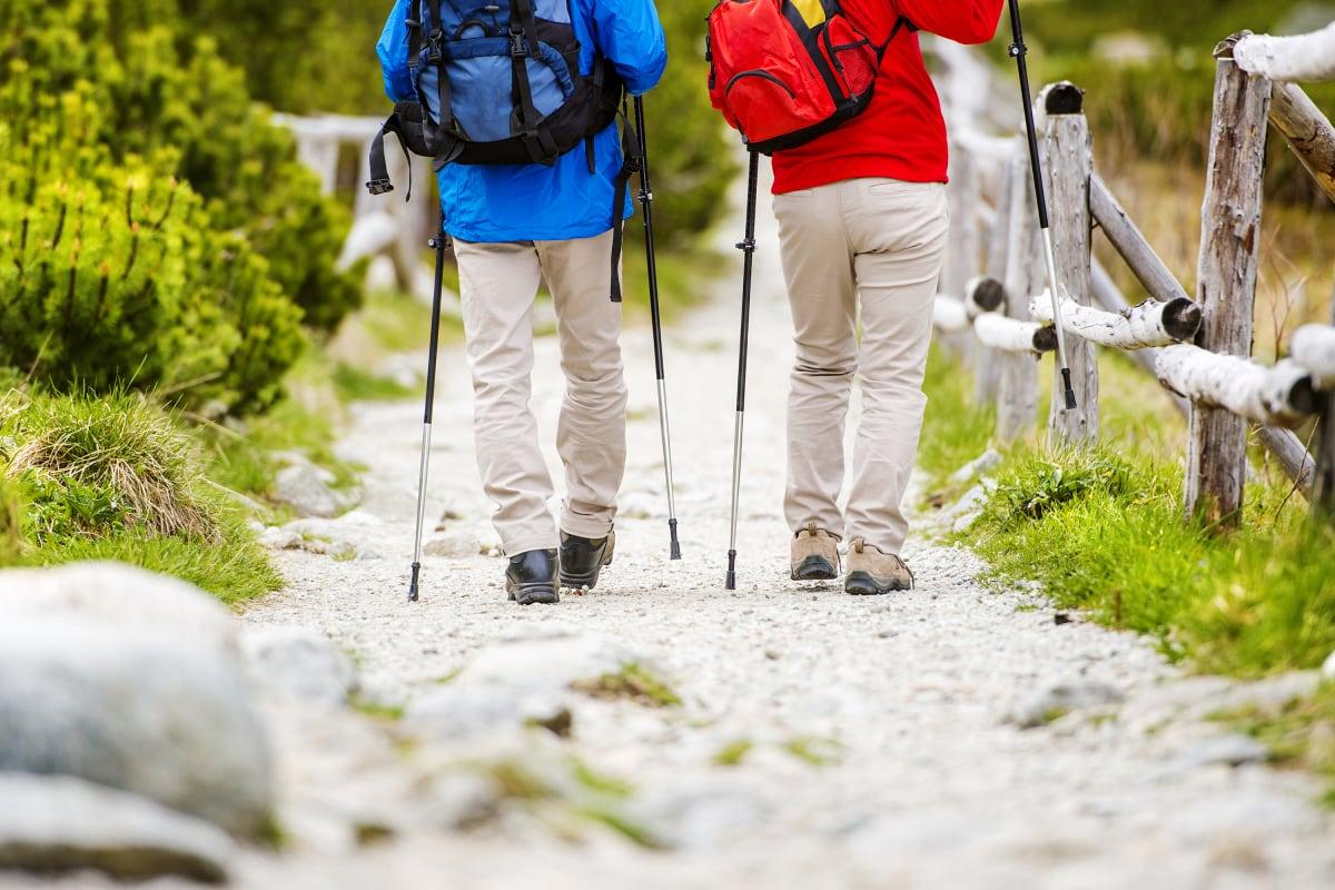 Arthrose-Patienten gehen einen Weg entlang mit Nordic Walking Stöcken