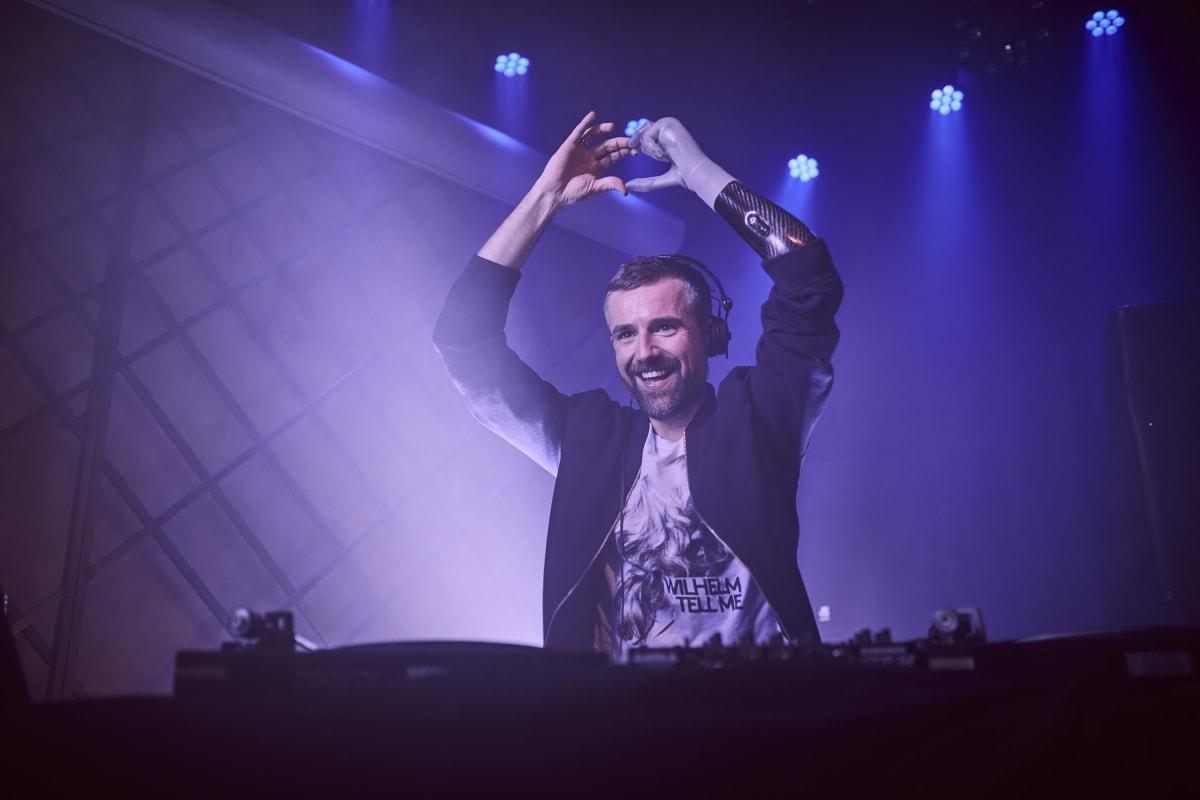 Bertolt steht hinter einem DJ Pult und formt mit seiner Handprothese i-Limb Quantum ein Herz
