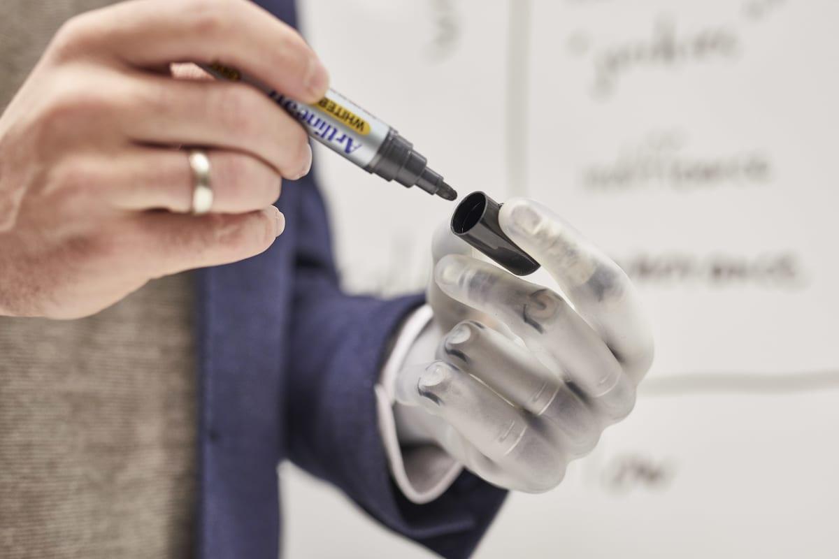 Bertolt als Professor in der Uni hält mit seiner Handprothese i-Limb Quantum einen Stift