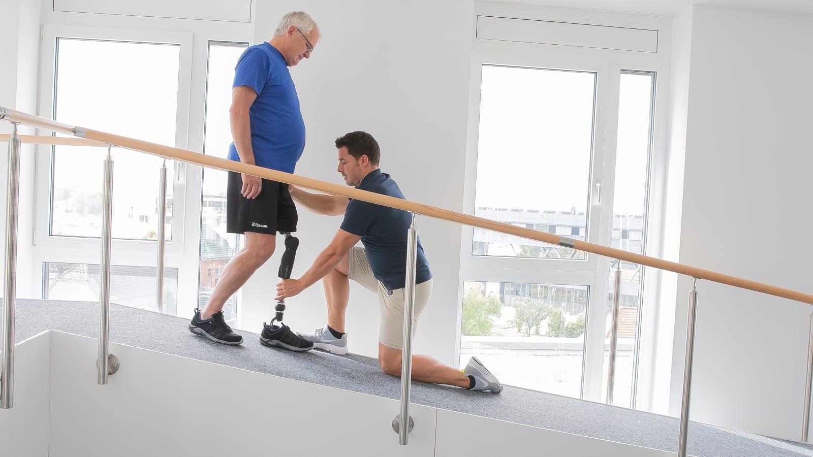 Therapeut und Prothesenträger auf einer Rampe während eines Anwendertrainings