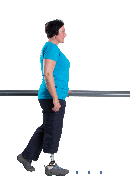 Markiere 3 verschiedene Punkte auf dem Boden. Belaste die Prothesenseite und gehe mit dem Fuß der Gegenseite einen Schritt.