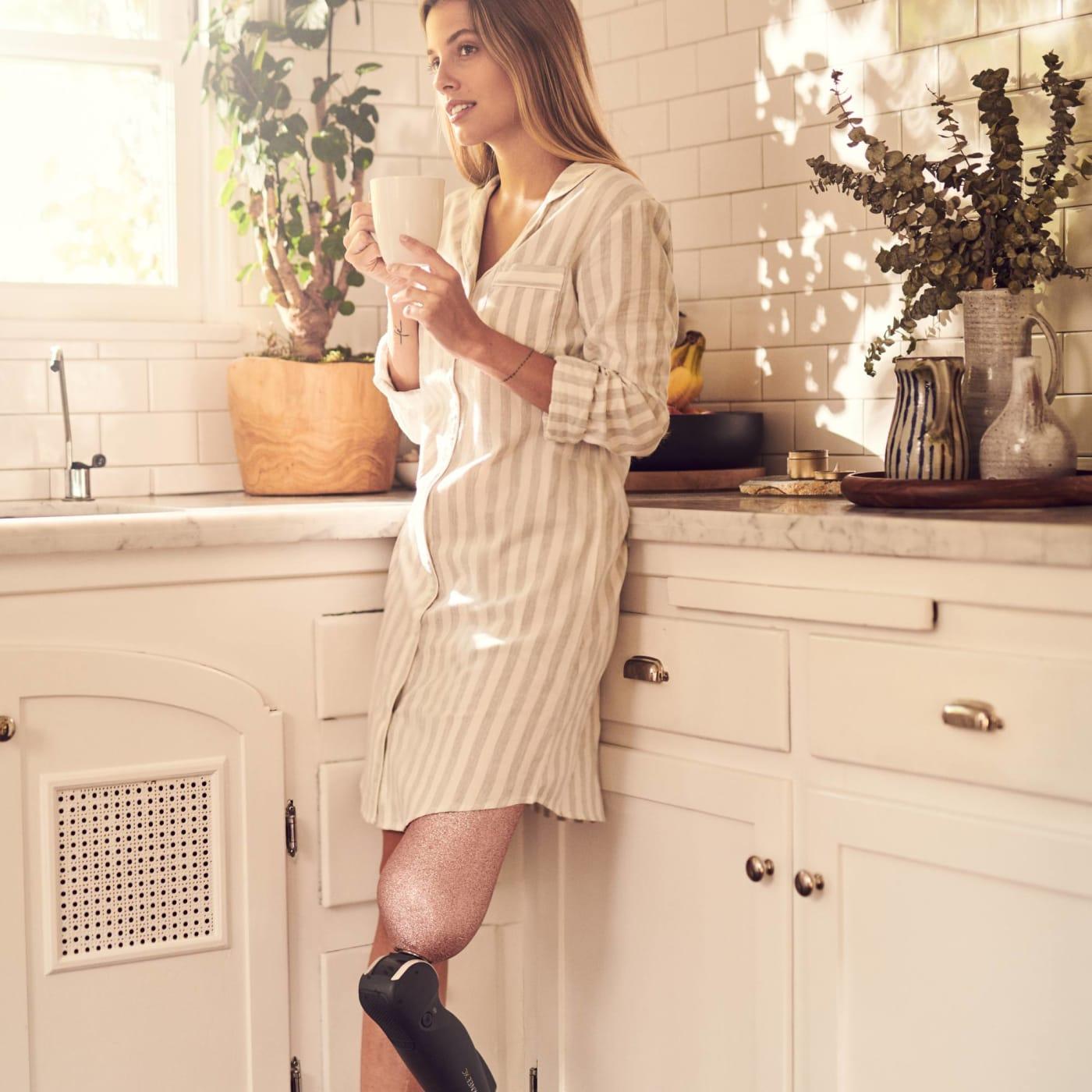 Paola Antonini steht in ihrer Küche mit einer Tasse Tee und trägt ihre Beinprothese