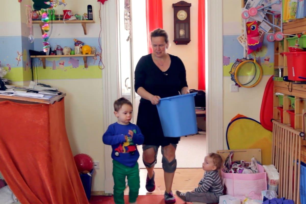 Kniearthrose-Patientin mit zwei Unloader One Knieorthesen bei ihrer Arbeit als Tagesmutter