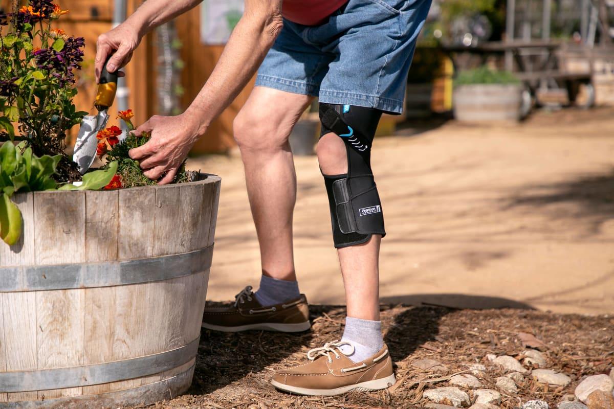 Man with Osteoarthritis gardening outdoors wearing black and blue Formfit OA Wraparound Knee Brace.