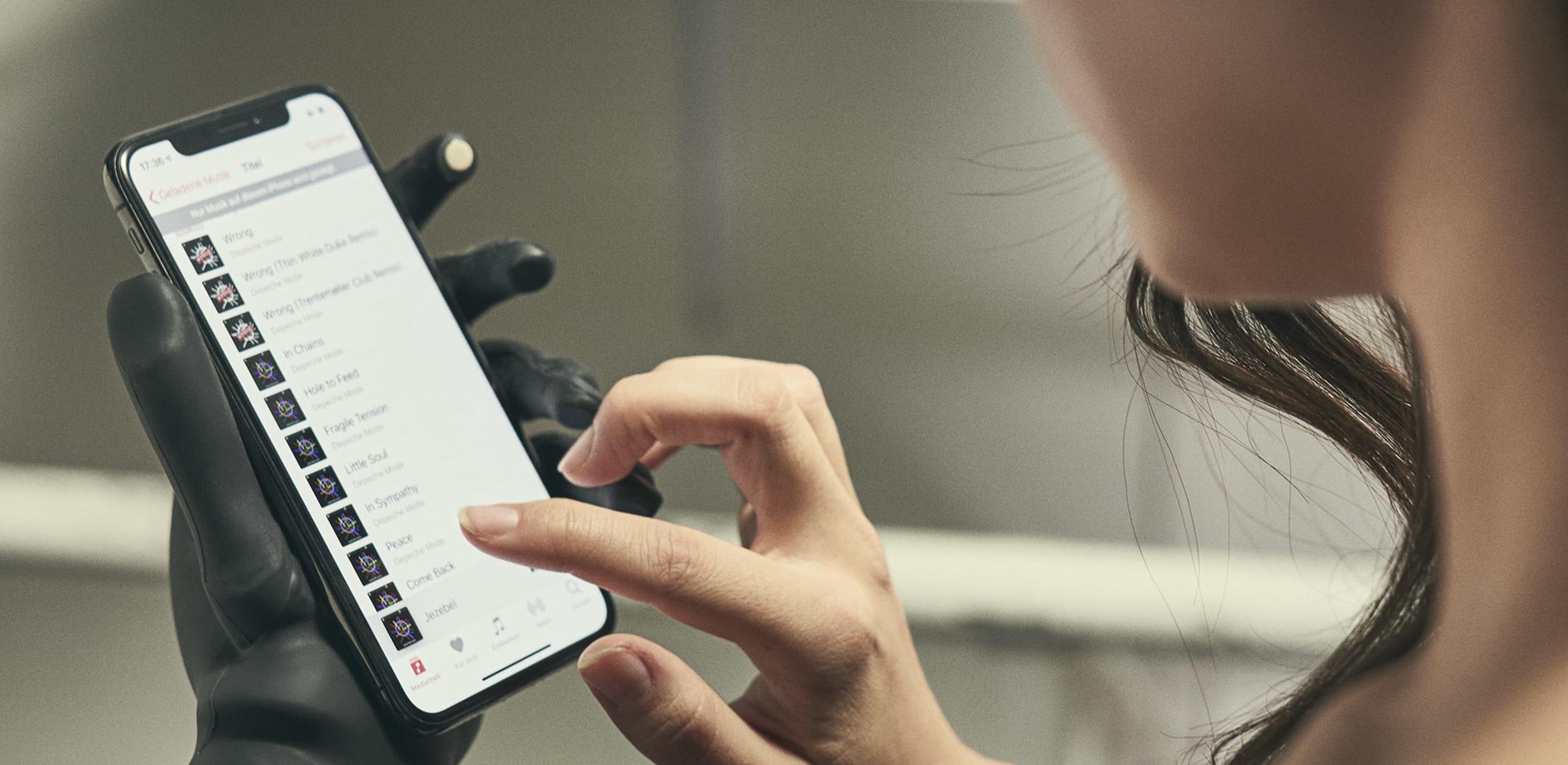 Shiori hält mit ihrer Handprothese i-Limb Quantum ein Smartphone fest